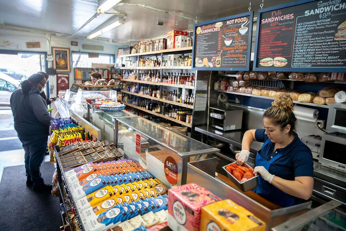 Sofia Saavedra stores food for closing hours as customers buy merchandise at Ted's Market & Deli on Tuesday, March 24, 2020, in San Francisco, Calif.