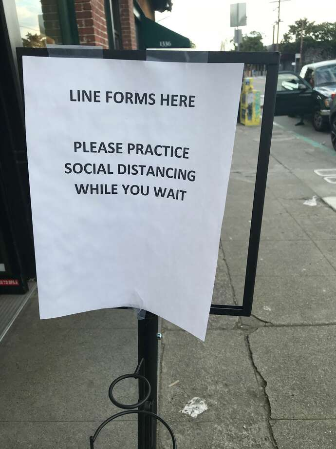 """The  beginning of the line outside Natural Grocery in Berkeley requests """"social distancing"""" as people wait to enter. Photo: David Curran"""