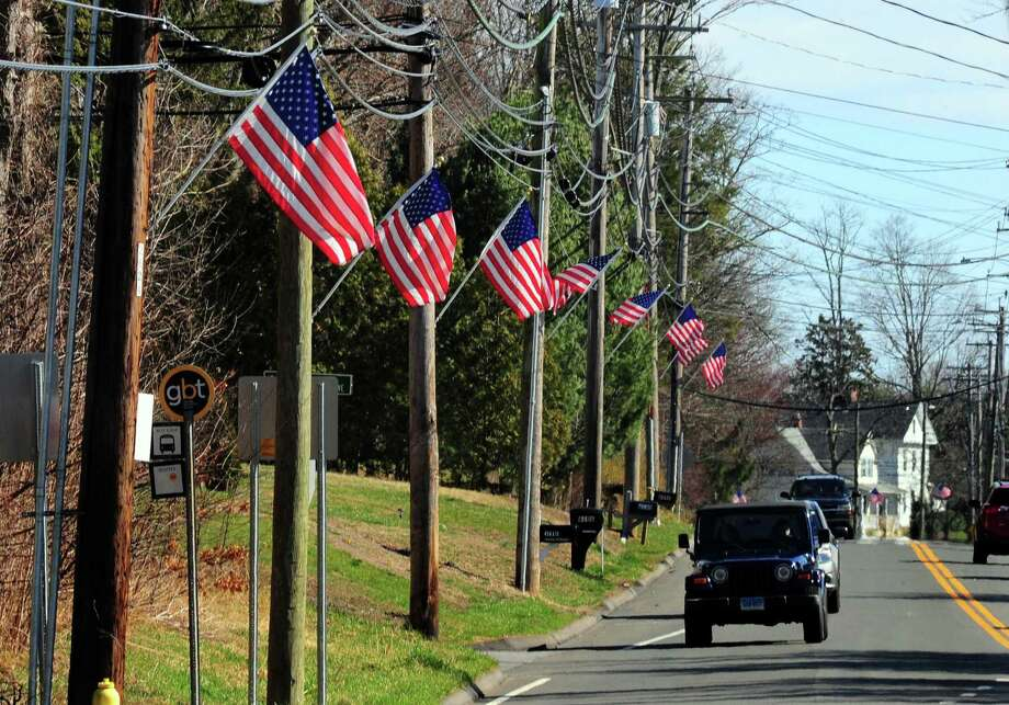 US flags line Main Street in Trumbull, Conn., on Tuesday Mar. 24, 2020. City public works crews, who usually put the flags up for the Memorial Day holiday, put them up again to rally the country to fight the coronavirus. Photo: Christian Abraham / Hearst Connecticut Media / Connecticut Post