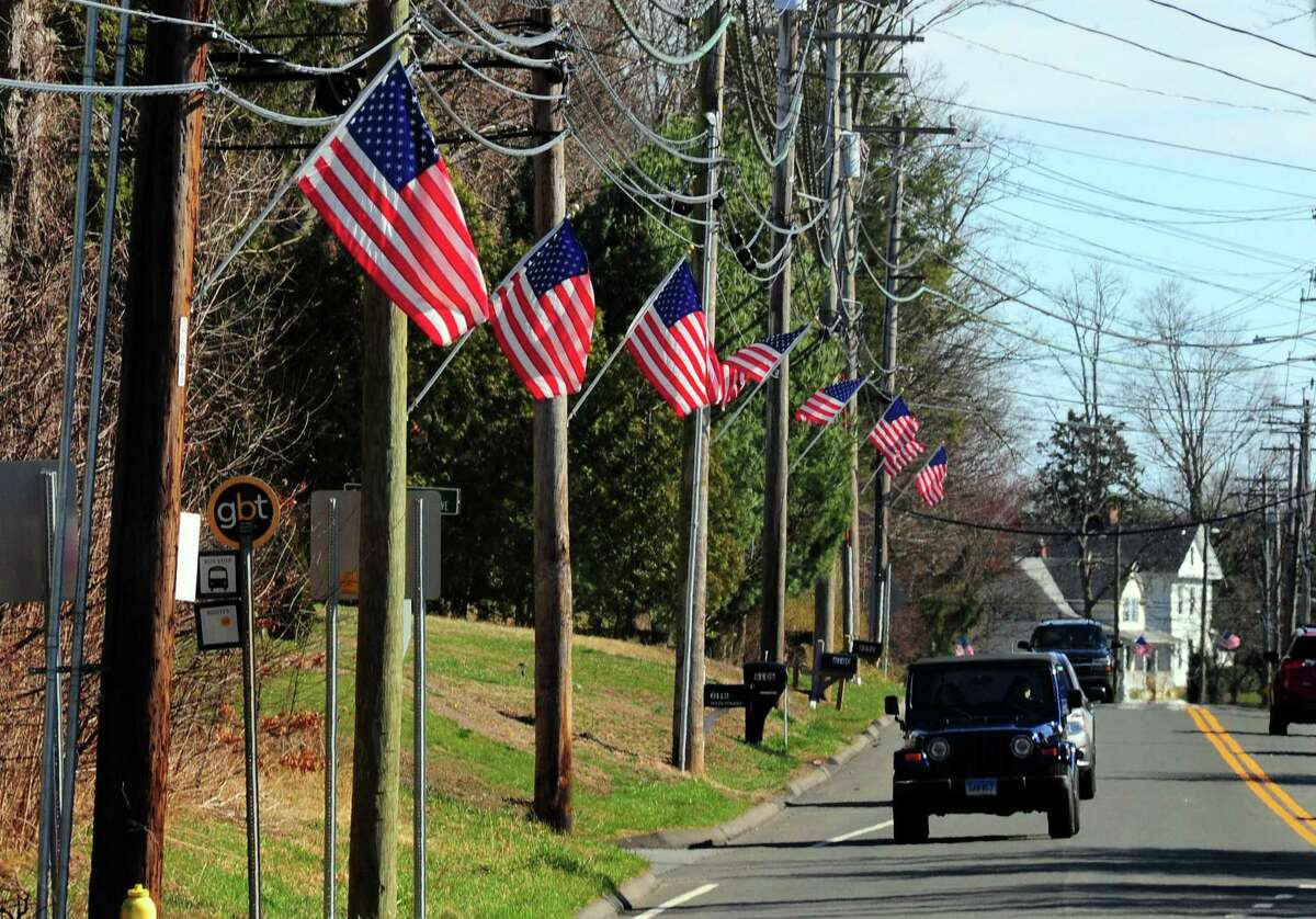 American flags line Main Street in Trumbull, Conn., on Tuesday Mar. 24, 2020.