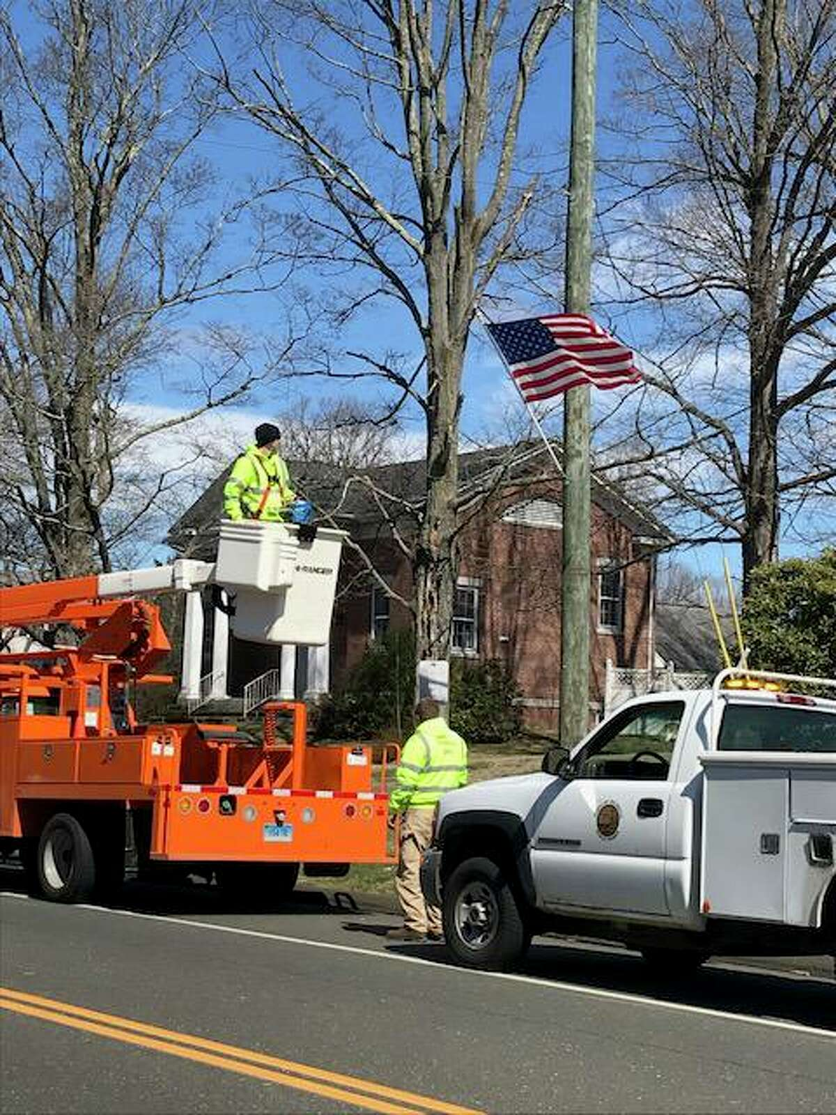 Workers hang American flags from utility poles along Main Street Tuesday afternoon.