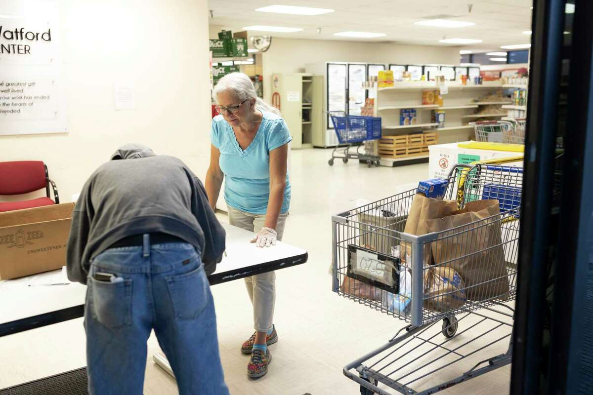 Paula Stoebner assists Gary P. Murray at te Northwest Assistance Ministries Watford Nutrition Center in Tomball, Friday, March 20, 2020. Northwest Assistance Ministries Watford Nutrition Center has noticed a three times increase in families and residents seeking assistance from the food pantry.