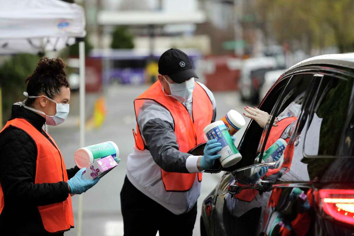Volunteers Keshia Link, left, and Dan Peterson reach for disinfectant wipes from a driver at a drive-up donation site for medical supplies at the University of Washington to help fight the coronavirus outbreak Tuesday, March 24, 2020, in Seattle.