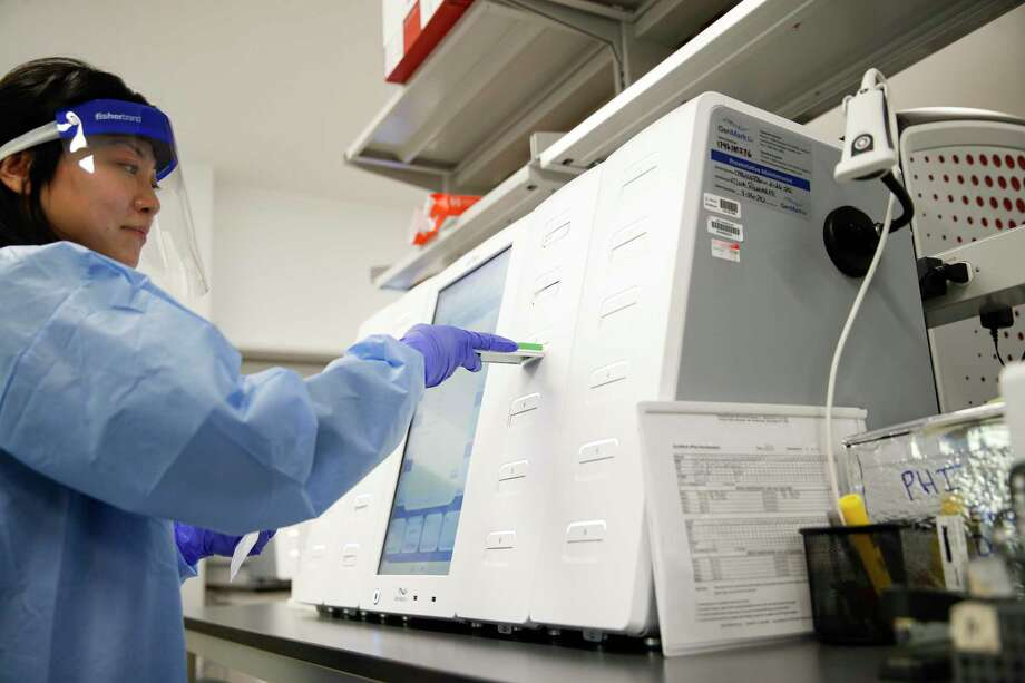 A lab technician prepares COVID-19 patient samples in Lake Success, N.Y., as U.S. companies dive into the search for a cure with the Food & Drug Administration promising to fast-track trials and approvals. (AP Photo/John Minchillo) Photo: John Minchillo / Associated Press / Copyright 2020 The Associated Press. All rights reserved.