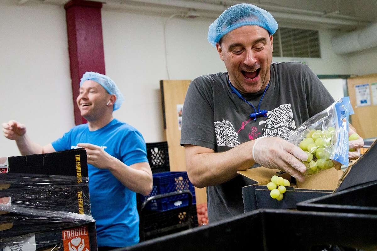 Grocery Services Supervisor Daniel Cohen (right) gets excited at the sight of grapes as he and Operations Director Michael McCormick (left) sort through fruit boxes donated by The Fruit Guys while in the volunteer space at Project Open Hand San Francisco, Calif. Wednesday, March 25, 2020. The Fruit Guys have found themselves with way too much fruit because their customers, mostly offices, who order their $50 fruit baskets have stopped ordering due to the shelter-in-place order issued amid the outbreak of the Coronavirus.