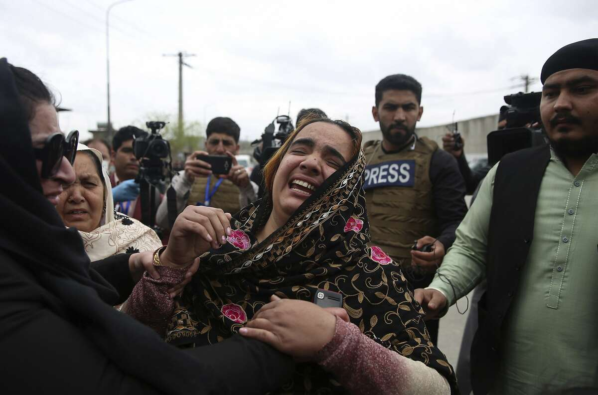 Family members cry after an attack in Kabul, Afghanistan, Wednesday, March 25, 2020. Gunmen stormed a religious gathering of Afghanistan's minority Sikhs in their place of worship in the heart of the Afghan capital's old city on Wednesday, a minority Sikh parliamentarian said. (AP Photo/Rahmat Gul)