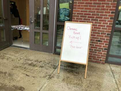A sign at Mauro-Sheridan School shows families where to go to pick up laptops during an extended building closure on March 23, 2020.