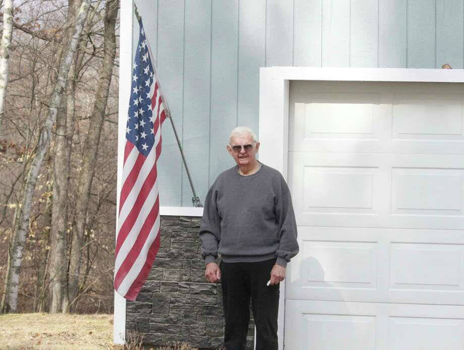 Dean Birch stands next to his American flag. He put the flag out several days ago to show his support of those fighting the spread of the coronavirus. (Pioneer photo/Catherine Sweeney)