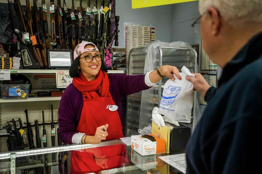 In this file photo from February, Belinda Kuchek hands a bag of doughnuts to a customer at Ace Hardware & Sports in Midland. The store began selling doughnuts from Cops & Doughnuts this winter, and sales have slowed since the coronavirus outbreak spread to Michigan. (Katy Kildee/kkildee@mdn.net)