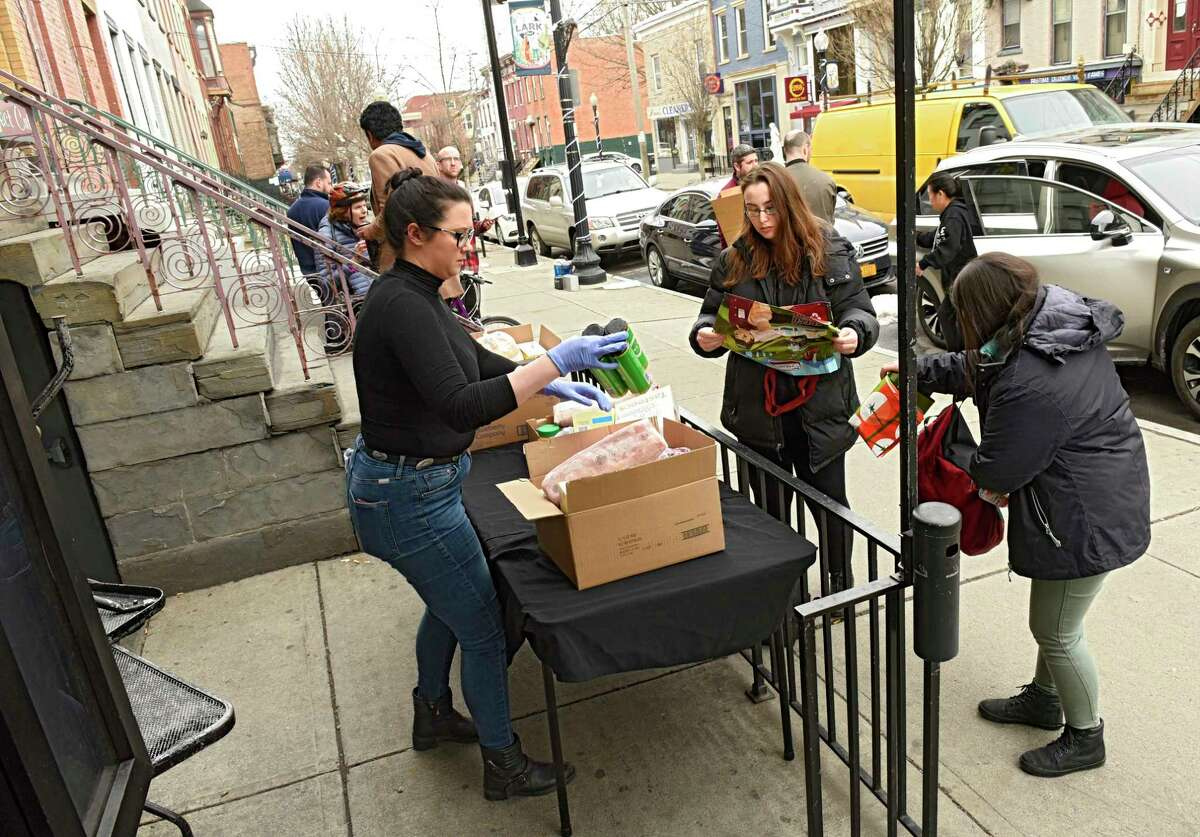 Emma Sawyer, left, general manager of Savoy, volunteers with the Feed Albany program in front of the restaurant Savoy on Lark St. Wednesday, March 25, 2020 in Albany, N.Y Feed Albany is a COVID-19 relief program to help people in need such as restaurant workers who are unemployed due to the coronavirus. (Lori Van Buren/Times Union)