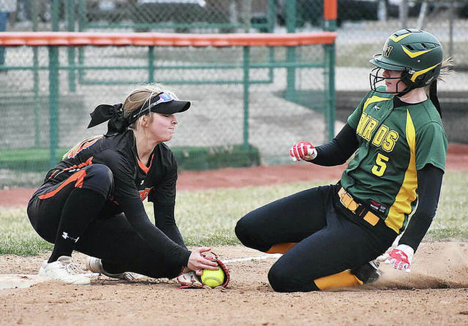 Edwardsville third baseman Lexi Gorniak (left) looks to apply the tag on Southwestern's Bailee Nixon, who gets to the bag safe for a triple in a game last season at Edwardsville. Photo: Matt Kamp | For The Telegraph