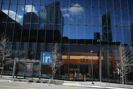 Part of the San Francisco skyline is reflected in the Linked In building as a person walks out the entrance at 222 Second Street on Wednesday, March 25, 2020 in San Francisco, Calif.