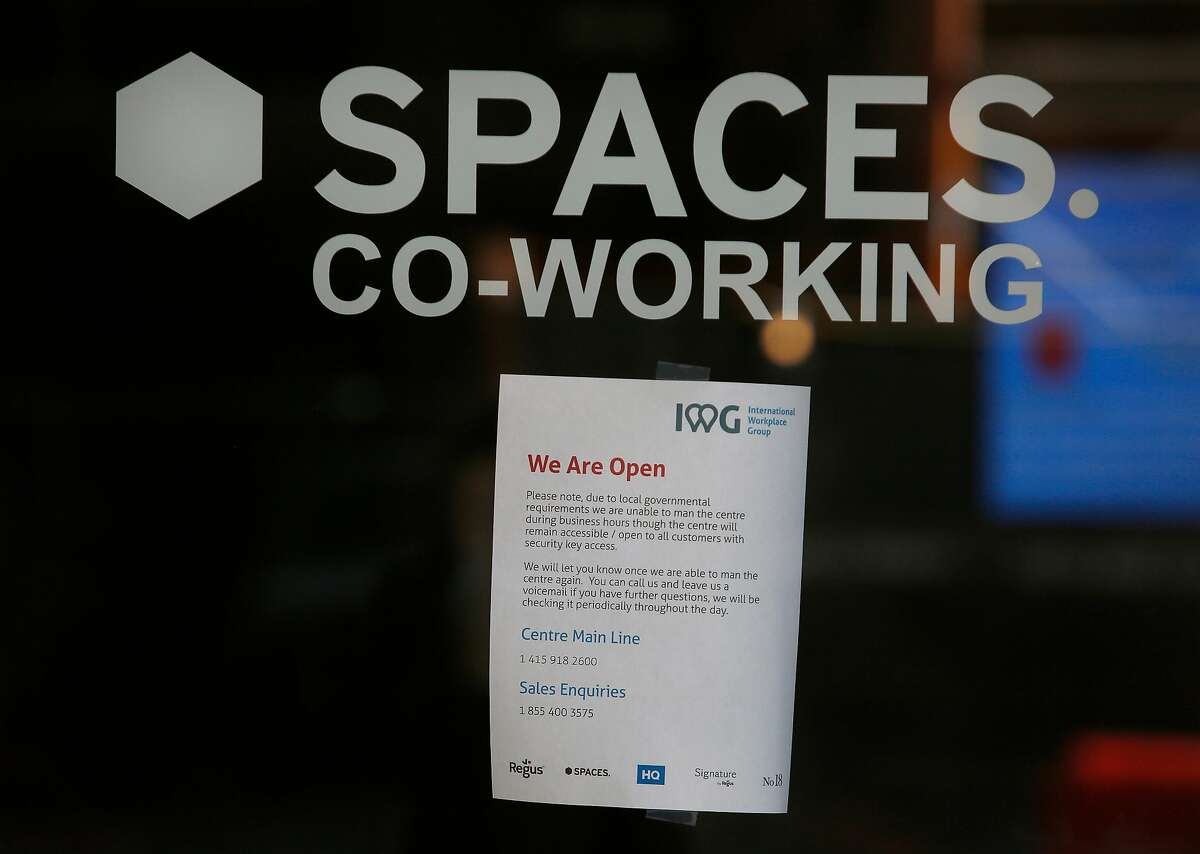 A sign on the door at Spaces at 95 Third Street alerts people to changes due to local governmental requirements on Wednesday, March 25, 2020 in San Francisco, Calif.