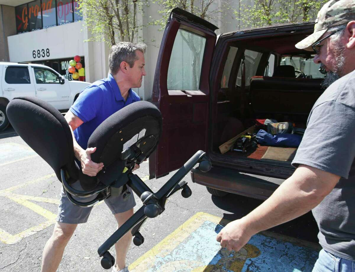 Erik Darmstetter, owner of Office Furniture Liquidations loads an office chair for a customer on March 25, 2020.