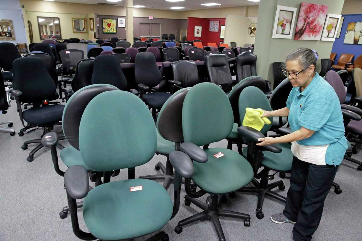 Rose Lopez does a cleaning pass on rows of chairs at Office Furniture Liquidations on March 25, 2020.
