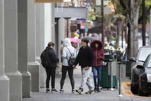 Pedestrians walk on Telegraph Avenue during the coronavirus shelter-in-place order in Berkeley, Calif. on March 25, 2020.
