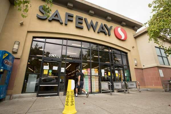 People walk into a Safeway grocery store during the coronavirus shelter-in-place order in Oakland, Calif. on March 25, 2020.