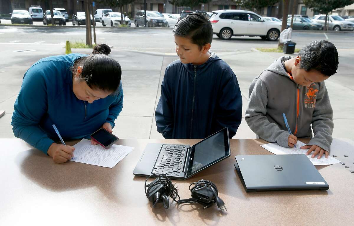 Maria de Jesus fills out paperwork with her son, Joshua Garcia (center) and his friend Pablo Carrillo (right), both sixth graders at Burbank Elementary School, before they pick up Chromebooks in Hayward, Calif. on Wednesday, March 25, 2020. About 150 of the laptops were made available for students to participate in their school studies while sheltering at home during the coronavirus pandemic.