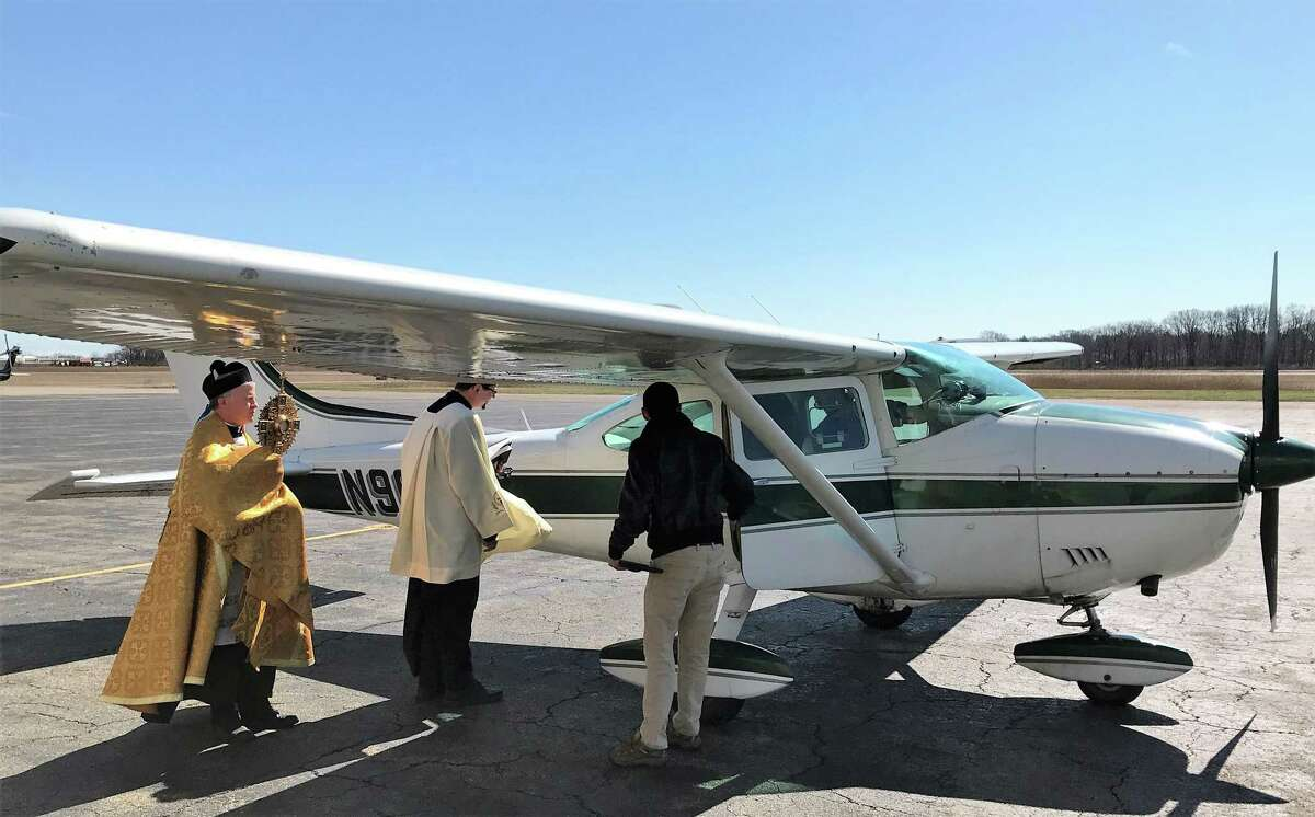 The Rev. Brian Gannon, pastor of St. Theresa's Roman Catholic Church in Trumbull and the Rev. Flavian Bejan, associate pastor enter the Cessna 172 airplane at Sikorsky Memorial Airport before flying over the Bridgeport Diocese to bestow blessings Tuesday afternoon.