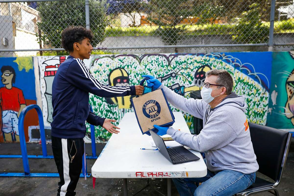 Luis Irigoyen, 15, (left) picks up a Chromebook from Chris Armentrout, the Director Policy & Planning at SFUSD at June Jordan High School on Wednesday, March 25, 2020 in San Francisco, California. School officials were distributing Chromebooks to students so they can continue their work during the coronavirus closure.
