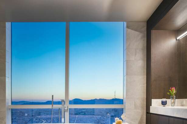 The Avery's grand penthouse residence enjoys a spa bathroom whose freestanding soaking tub rests beside floor-to-ceiling windows framing views of Sutro Tower.