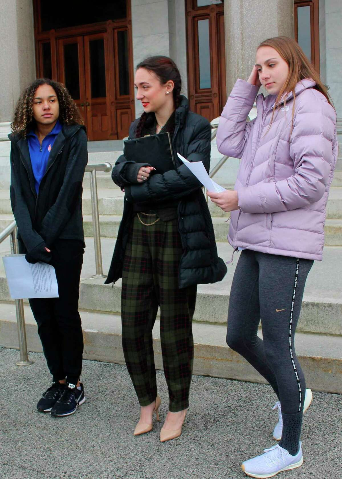 From left, high school track athletes Alanna Smith, Selina Soule and Chelsea Mitchell prepare to speak at a news conference outside the Connecticut State Capitol on Feb. 12. The girls filed a federal lawsuit to block a state policy that allows transgender athletes to compete in girls sports.