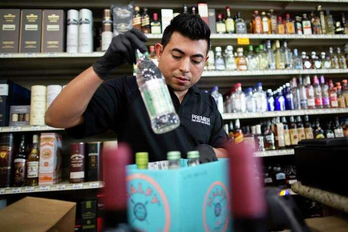 Premier Fine Wine & Spirits' employee Charlie Lara prepares a deliver order on Wednesday, March 18, 2020, in Houston.