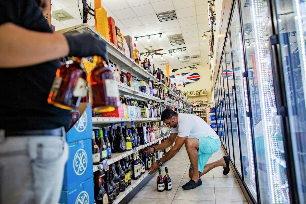 Premier Fine Wine & Spirits' owner Suraj Singh restocks his liquor store on Wednesday, March 18, 2020, in Houston.