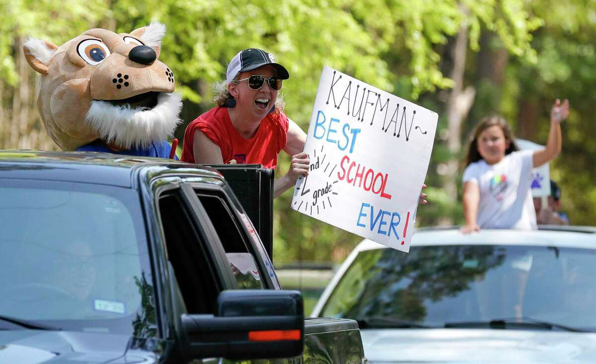 Second grade teacher Stephanie Shaw cheers as teachers with Kaufman Elementary School take part in a parade through nearby neighborhoods, Wednesday, March 25, 2020, in Spring.