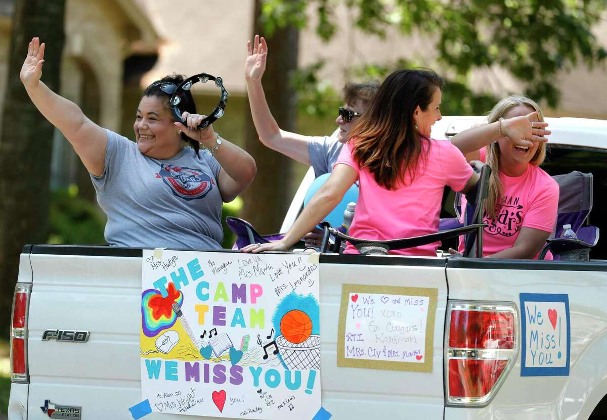 Teachers with Kaufman Elementary School take part in a parade through nearby neighborhoods, Wednesday, March 25, 2020, in Spring.