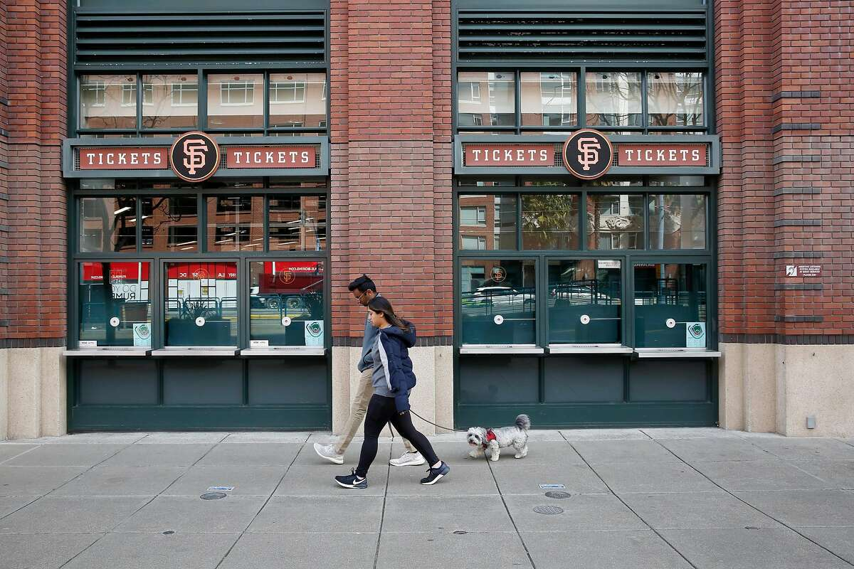 Pedestrians walk past the ticket windows at the box office at Oracle Park on Tuesday, March 17, 2020 in San Francisco, Calif.