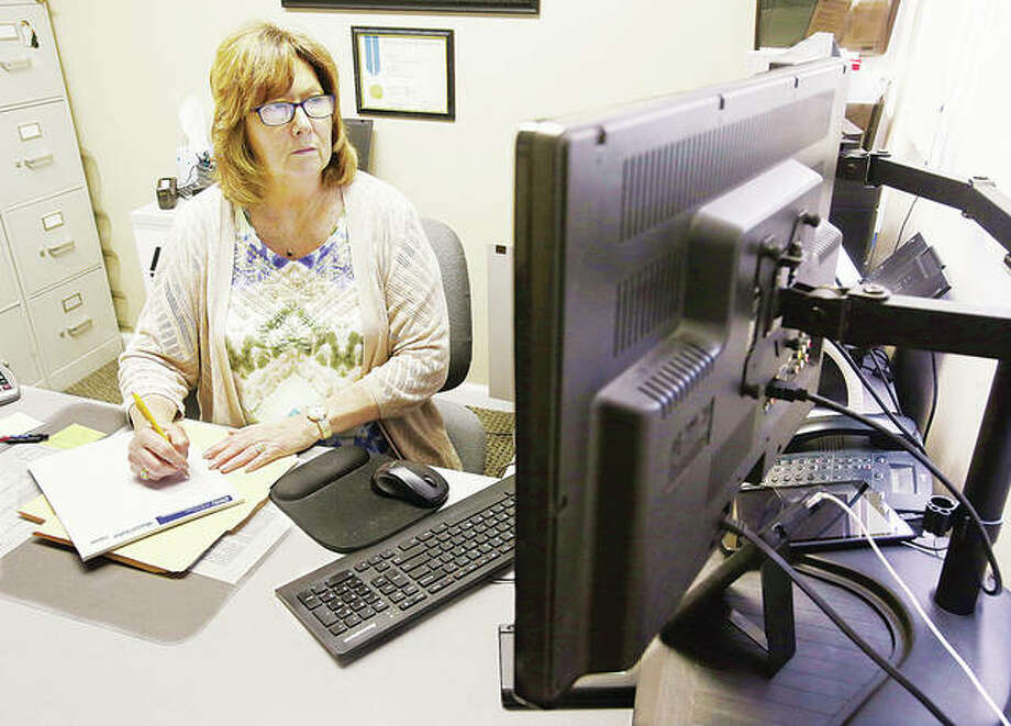 Wanda Jockisch, of ActionTax at 5411 E, Godfrey Road in Godfrey looks at the computer screen Wednesday in her office at the tax preparation business. Some tax preparers are only accepting drop-off tax forms due to concerns of the COVID-19 virus.