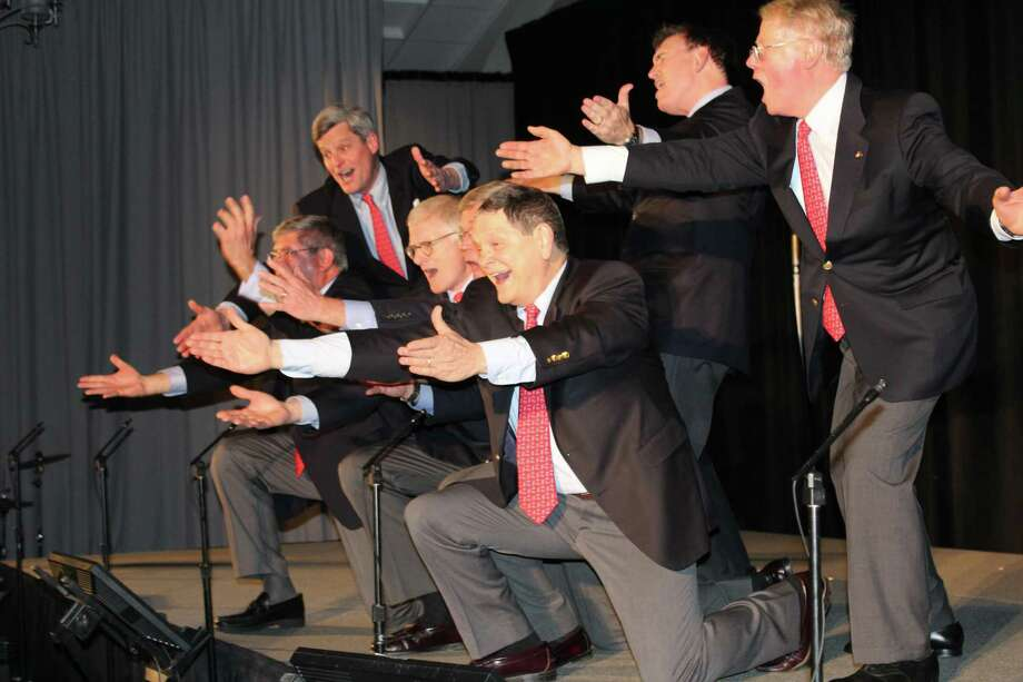 The men are dressed in suit and tie for the finale of a previous Gridiron Club of New Canaan show at the Italian American Club in Stamford. The actors left to right are Steve Pond, Bill Walbert, Eric Thunem, Bruce Wilkinson, John Walsh, Tom Butterworth, and Robert Curry. After discussion of all considerations, the club's Board of Directors has decided to postpone its 2020 show. It will now take place October 30, 2020. Photo: Ava Nichols / Contributed Photo / Connecticut Post