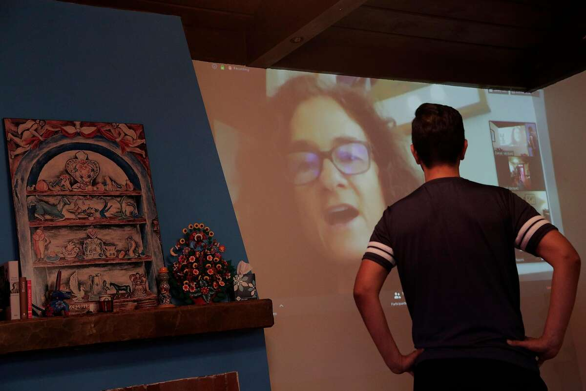 Daniel Vasquez looks up at a projection of trainer Kym Sterner as he works out in his living room during a streamed class by Sweat in Place using Zoom to share workouts remotely in Oakland, Calif., on Tuesday, March 24, 2020.