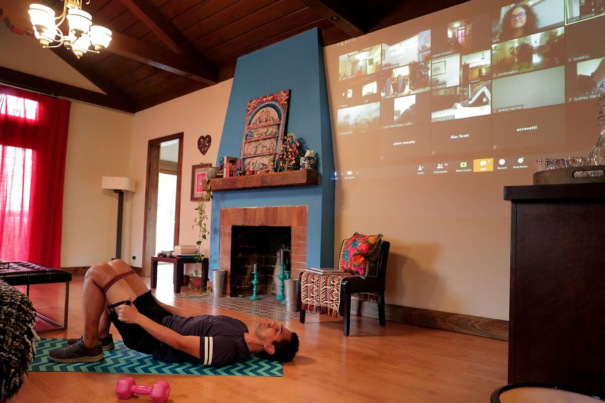 Daniel Vasquez works out in his living room during a streamed class by Sweat in Place using Zoom to share workouts remotely in Oakland, Calif., on Tuesday, March 24, 2020.