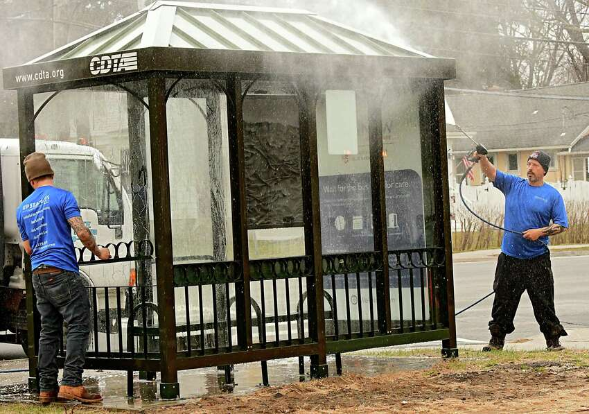 Employees from Upstate Pressure Cleaning sanitize and disinfect a CDTA bus stop enclosure along Western Ave. on Wednesday March 25, 2020 in Albany, N.Y They were cleaning all the CDTA bus stops. (Lori Van Buren/Times Union)
