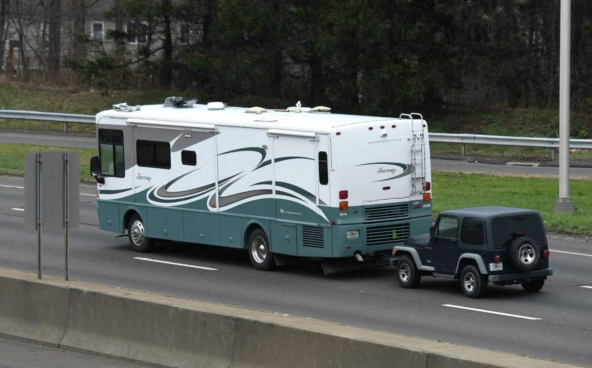An RV towing a Jeep passes by Exit 4 on I-95 on Wednesday. With the coronavirus epidemic at hand, many people are leaving the area to stay in remote rental homes or second homes away from populated areas.