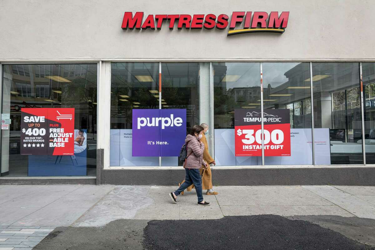 Pedestrians walk past a Mattress Firm Holdings Corp. store in San Francisco, California, U.S., on Tuesday, March 24, 2020. Governors from coast to coast Friday told Americans not to leave home except for dire circumstances and ordered nonessential business to shut their doors.
