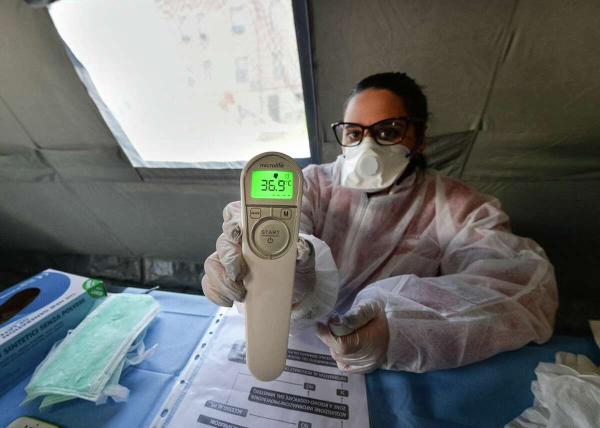 One of the most basic tools for diagnosis of COVID-19 has been the thermometer. A key indicator of whether someone might be infected with the virus is a fever. Here, a Red Cross volunteer uses a digital thermometer to measure patients' temperatures in a pretriage tent outside the hospital in Corigliano-Rossano, Italy, on March 11.