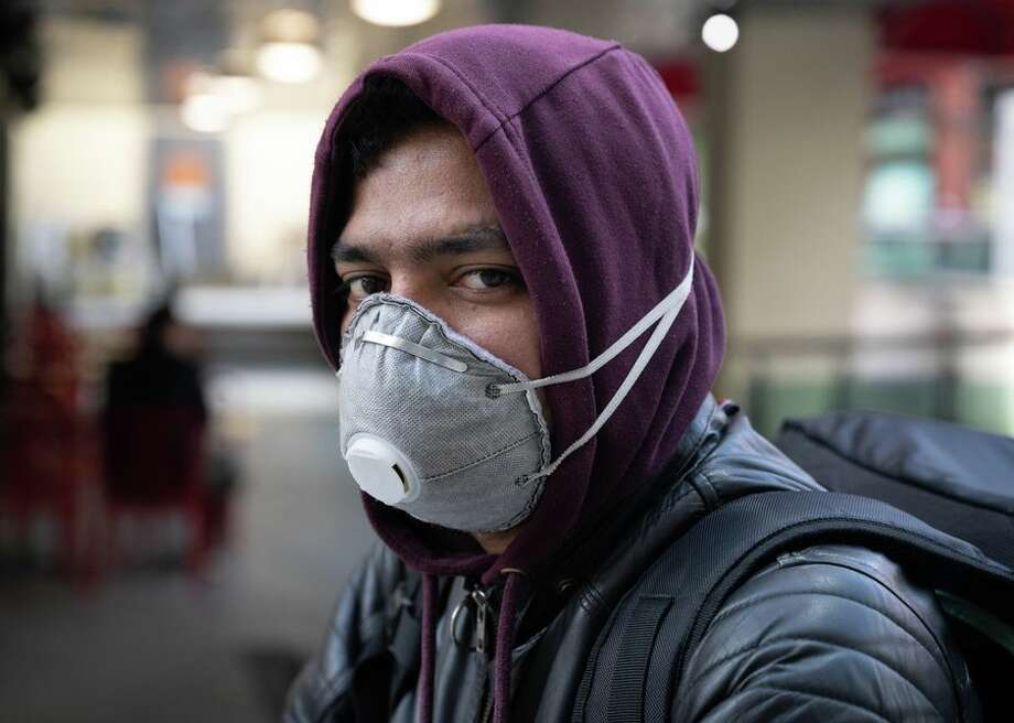 A food delivery worker in Cardiff, Wales, is seen wearing an N95 mask on March 8. Although many Laredoans immediately condemned the idea, starting Thursday they will have to wear something that covers their nose and mouth if they enter any building that is not their house, such as H-E-B, gas stations and even their place of work. Photo: CBSI/CNET