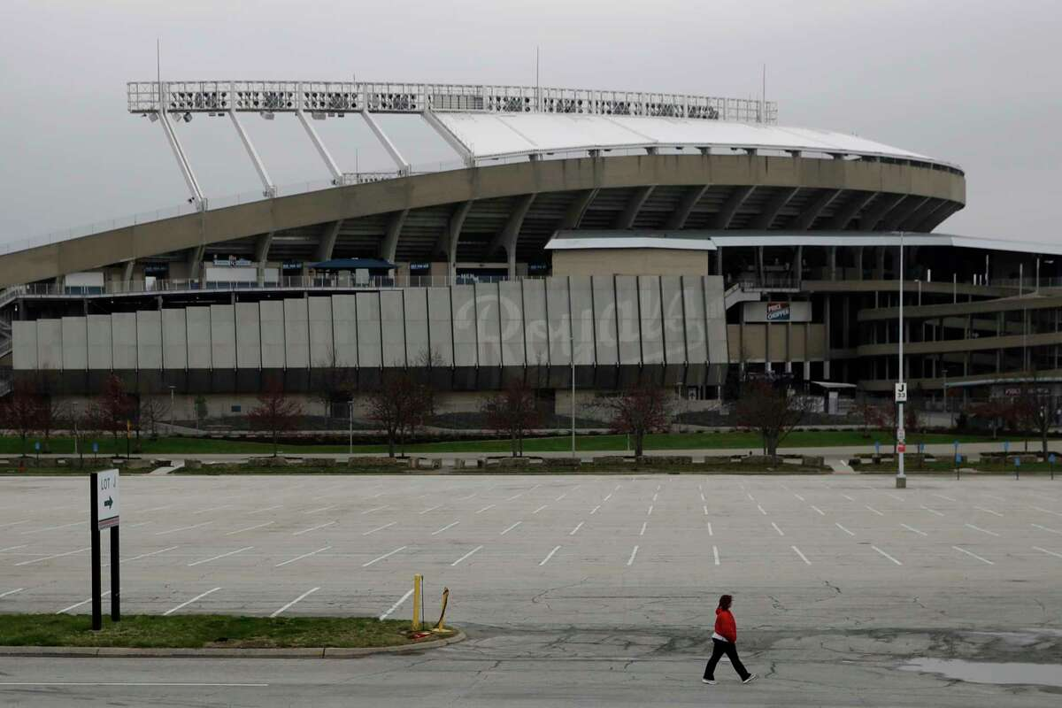 A woman walks past Kauffman Stadium, home of the Kansas City Royals baseball team, Wednesday, March 25, 2020, in Kansas City, Mo. The start of the regular season, which was set to start on Thursday, is on hold indefinitely because of the coronavirus pandemic. (AP Photo/Charlie Riedel)