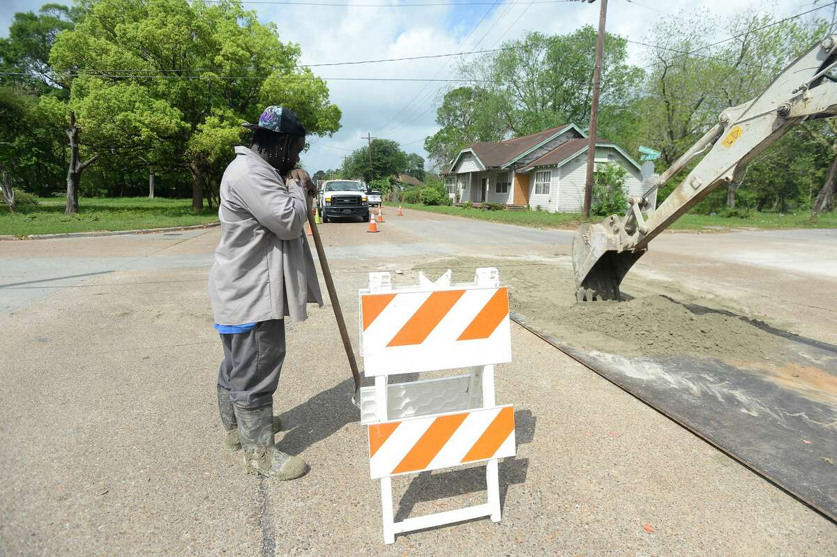 Byron Morris directs traffic as he and Travis Guidry work on repairing a manhole and resurfacing on Lavaca Street Tuesday. Photo taken Tuesday, March 24, 2020 Kim Brent/The Enterprise