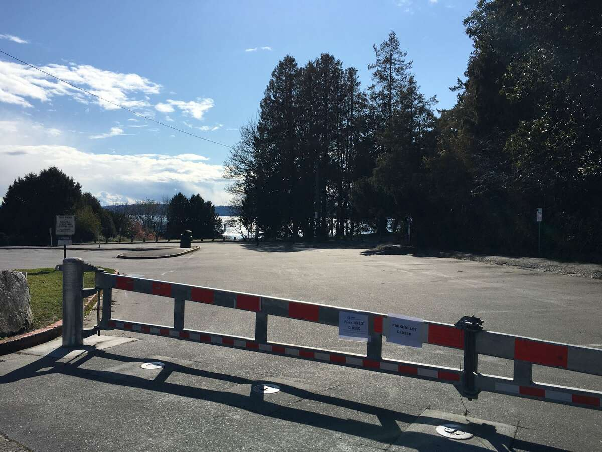 A closed gateand signs posted atthe parking lot entrance of Lincoln Park in West Seattle, Wash. on March 25, 2020. The parking lot was closed in an effort to increase social distancing and prevent gatherings inthe parking lot underGov.Inslee'sstatewide