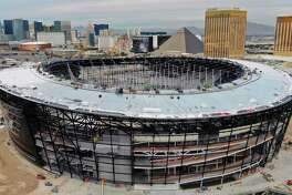 This Dec. 18, 2019 photo shows an aerial view of Allegiant Stadium ,the new NFL football stadium under construction in Las Vegas. A person familiar with the team's plans says the Oakland Raiders have declined an option to remain in Oakland for 2020 and are on target to move into the new stadium this summer. Construction on the stadium has been deemed an essential project and is going on without interruption despite most business being shut down in Nevada because of the new coronavirus. (Michael Quine/Las Vegas Review-Journal via AP)