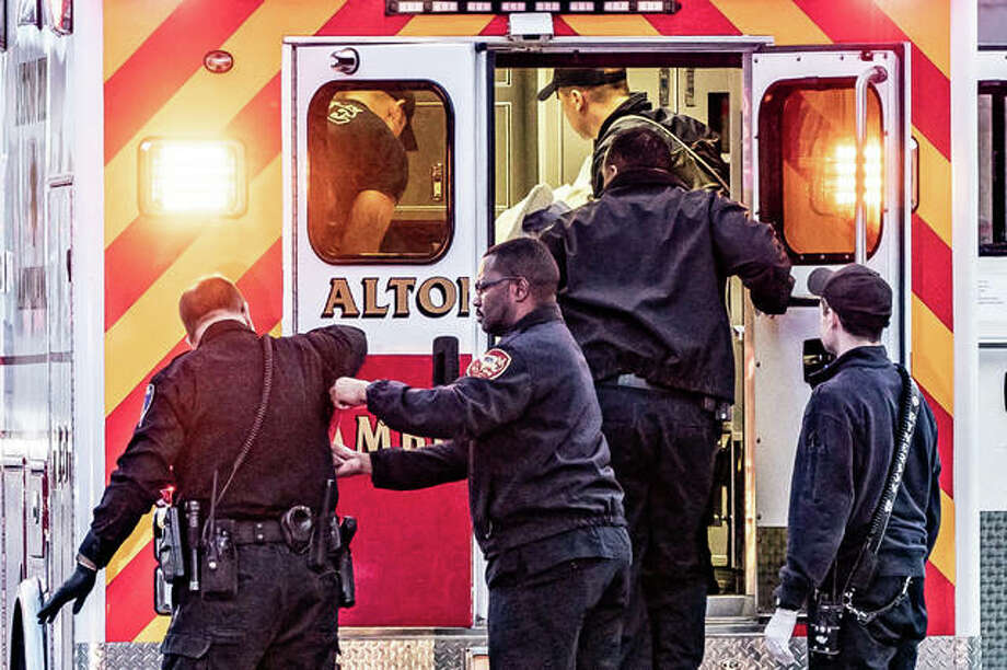 Alton firefighters and paramedics prepare the victim of a gunshot wound for transport to an Alton hospital Wednesday evening on Central Avenue, at Hellrung Park. He is expected to survive. Photo: Nathan Woodside | The Telegraph
