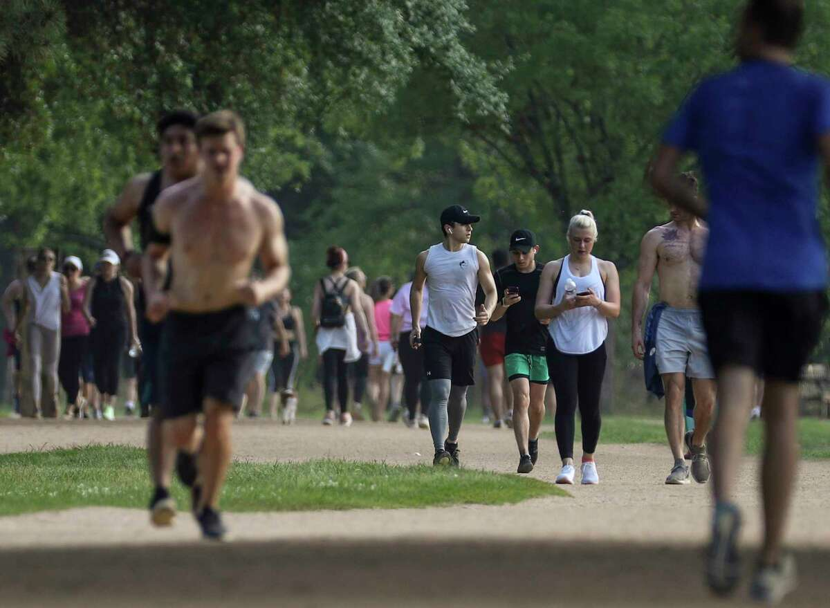 People exercise in Memorial Park on Tuesday, March 24, 2020, in Houston. City of Houston and Harris County officials issued a stay-at-home order on Tuesday due to concerns about the spread of COVID-19. The order is set to take effect at 11:59 p.m.