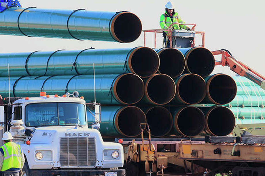 Workers unload pipes in Worthing, South Dakota, in 2015 for the Dakota Access oil pipeline that stretches from the Bakken oil fields in North Dakota to Illinois. A federal judge on Wednesday ordered the U.S. Army Corps of Engineers to conduct a full environmental review of the pipeline, nearly three years after it began carrying oil. Photo: Nati Harnik | AP