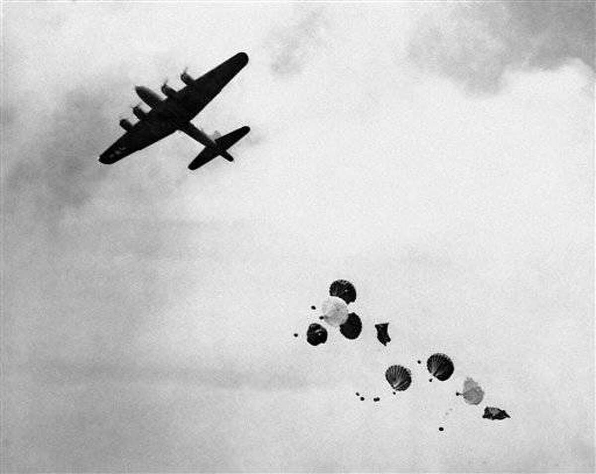 Parachutes loaded with supplies drop from a flying fortress to American invaders on Los Negros Island March 26, 1944, before any other means of supplying these men became available to be used instead of the usual transport planes because of the presence of enemy fighter craft, against which the transports( are not sufficiently armed. (AP Photo)