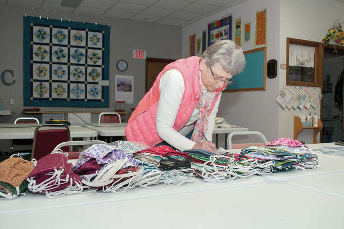 Sue Fox, owner of Times Square Sewing Complex, counts hospital-style masks Wednesday morning at her store. The masks, which have been handmade by local seamstresses, quilters and other fabric enthusiasts, will be donated to local nursing homes to help in the ongoing COVID-19 pandemic.
