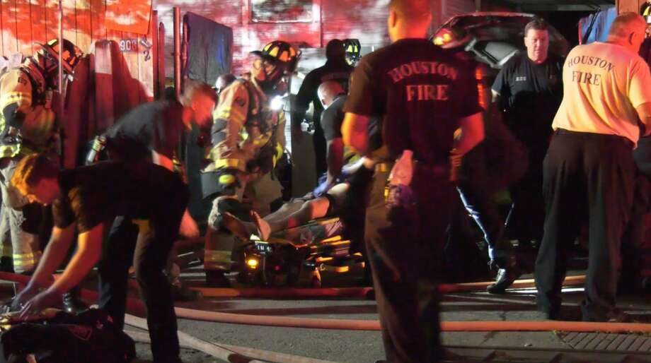 Firefighters perform CPR on a woman found inside a house fire in the 900 block of Walton on Thursday, March 26, 2020. Photo: OnScene.TV